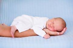 睡觉在他的父亲的胳膊的小男婴 免版税库存图片