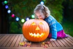 雕刻南瓜的小女孩在万圣夜 免版税库存照片