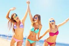 获得小组的妇女在海滩的乐趣 免版税库存照片
