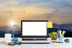 在书桌上的便携式计算机和风景观看背景 图库摄影