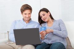 使用的膝上型计算机和在网上购物的信用卡的夫妇 免版税图库摄影