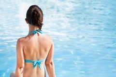 坐在游泳池边缘的妇女 免版税库存图片