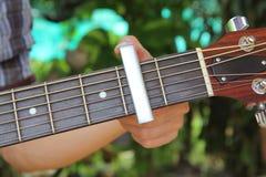 吉他弹奏者对吉他的别针品柱 免版税库存照片