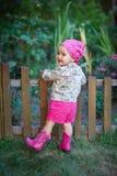 桃红色鞋子的小女孩在篱芭附近 免版税库存照片