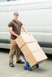 拿着有纸板箱的送货人台车 免版税库存照片