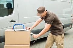 Коробки скеннирования работника доставляющего покупки на дом с блоком развертки штрихкода Стоковое фото RF