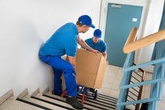 Δύο μετακινούμενοι με το κιβώτιο στη σκάλα Στοκ Φωτογραφίες