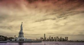 与纽约地平线的自由女神像在背景中 图库摄影