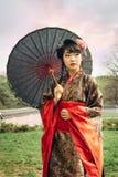 走在庭院里的美丽的亚裔妇女 免版税库存图片
