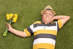 快乐资深说谎在草和拿着郁金香 免版税库存照片