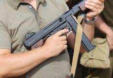 Ο στρατιώτης σε ομοιόμορφο με ένα πυροβόλο όπλο σε δικοί του παραδίδει το στρατόπεδο κατάρτισης Στοκ Εικόνα