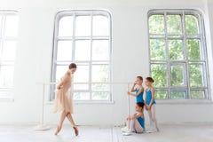 跳舞与个人芭蕾老师的三位小芭蕾舞女演员在舞蹈演播室 库存照片