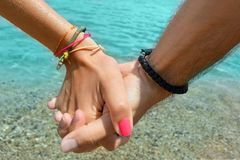 Пары держа руки на море Стоковые Изображения RF