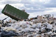 卸载垃圾的垃圾车在垃圾堆积场 免版税库存照片