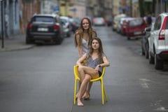 逗人喜爱的女孩坐椅子在老镇的街道中间 免版税库存图片