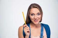 拿着铅笔的一名微笑的年轻学生的画象 免版税图库摄影