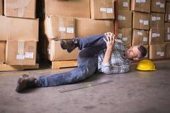 说谎在地板上的工作者在仓库里 免版税库存图片