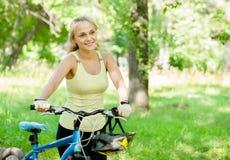 有山的微笑的妇女在公园骑自行车 免版税库存图片