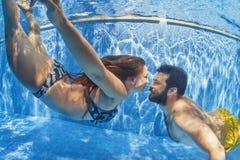 游泳在水面下在室外水池的正面夫妇 免版税库存图片