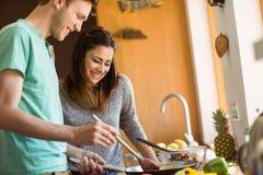 一起准备食物的逗人喜爱的夫妇 库存照片
