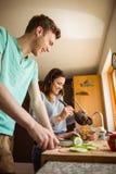 一起准备食物的逗人喜爱的夫妇 免版税库存照片