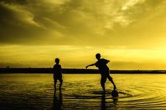 男孩戏剧在日落日出期间的海滩足球 库存照片