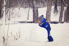 小男孩大厦雪人在冬天 库存照片