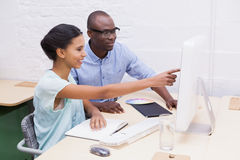 显示某事的妇女对她的膝上型计算机的同事 免版税库存照片