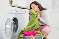 有衣裳的妇女在洗衣机附近 库存图片
