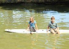 Девушка и мальчик играя на прибое Стоковая Фотография