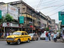 车和人们在街道上在加尔各答,印度 库存照片