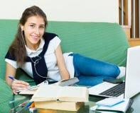 使用年轻人的女孩家庭膝上型计算机 库存照片