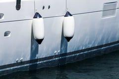 垂悬在白色游艇船身上的小船防御者 库存图片