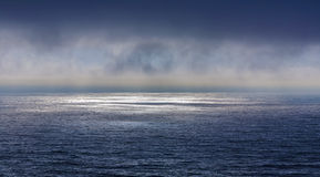 有黑暗的深云彩的美丽的海在日落 库存图片