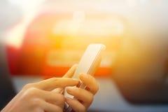 关闭使用流动巧妙的电话的妇女室外在停车场 免版税库存照片