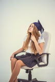 Школьница с студент-выпускником крышки сидит на стуле, думая о будущем Стоковые Изображения RF