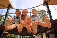 有他们的脚的孩子在天空中 免版税库存照片