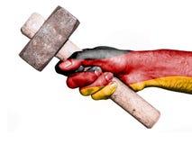 有处理一把重的锤子的德国的旗子的手 库存照片