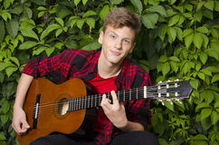 弹吉他的美丽的少年画象外面 免版税库存图片
