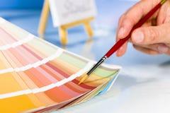 指向在调色板的颜色样品的艺术家手有油漆刷的 库存照片
