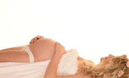 怀孕的斜倚的妇女 免版税库存照片