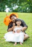 使用在与她的母亲的绿草的小亚裔女孩 免版税库存图片