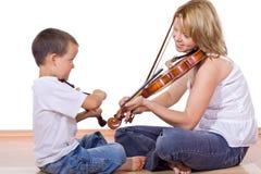男孩实践的小提琴妇女 免版税库存照片