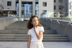 一个现代大厦的背景的女婴 免版税库存图片
