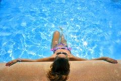 比基尼泳装和太阳镜晒日光浴的倾斜的可爱的妇女在度假胜地游泳池边缘  免版税库存图片