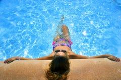 比基尼泳装和太阳镜晒日光浴的倾斜的可爱的妇女在度假胜地游泳池边缘  免版税库存照片
