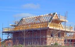 有屋顶椽木和脚手架的新的修造房子 免版税图库摄影
