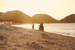 在海滩的骑马摩托车在日落 库存图片