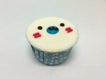 与设计的逗人喜爱的椰子味道杯形蛋糕当封印面孔 图库摄影