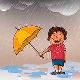 享用雨的逗人喜爱的男孩 图库摄影
